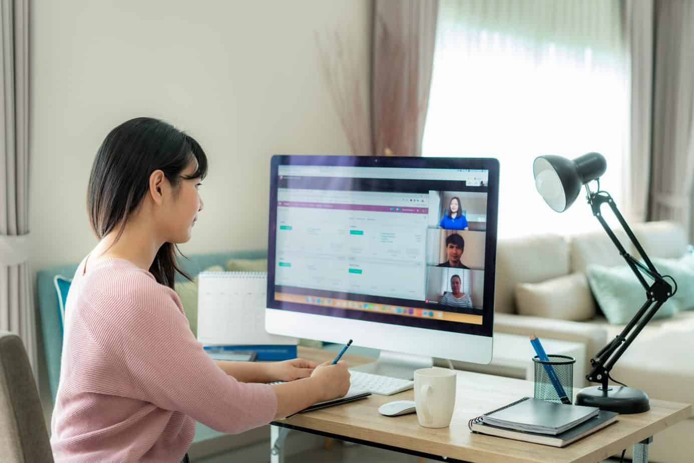 woman working from home on desk with large screen